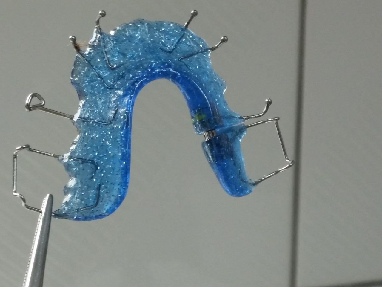 How does the Invisalign Invisible Brace work in straightening crooked smiles?